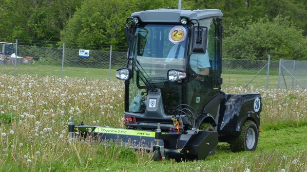 Front mounted flail mower for compact tractor is mowing the lawn