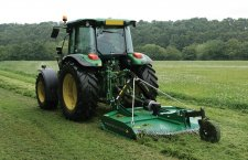 Finishing mower for tractor mows a field of grass
