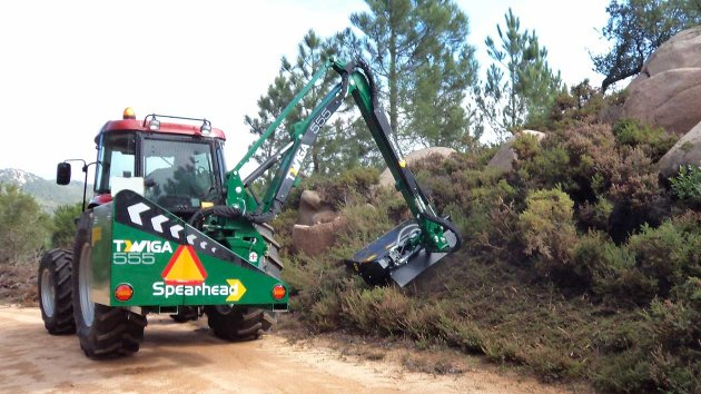 Arm mower working in rough terrain with rocks and stones
