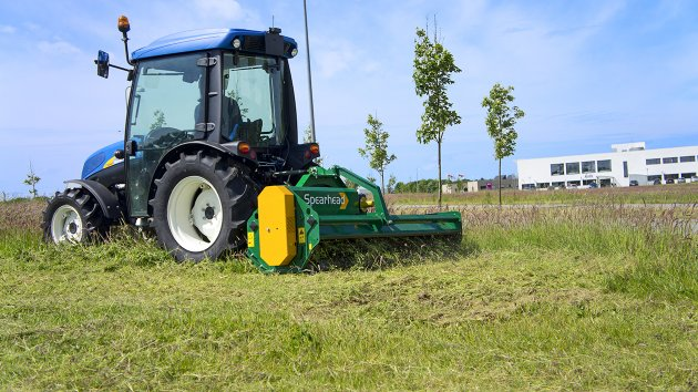 Flail mower for small tractor is mowing the lawn