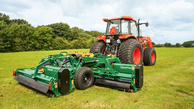 Trailed flail mower is mowing a field of grass