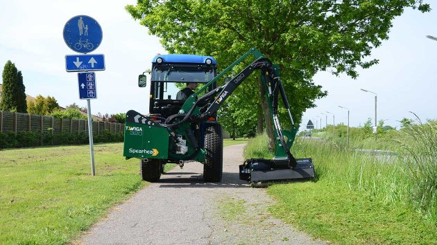 Boom mower mounted on a compact tractor with attached flail mower