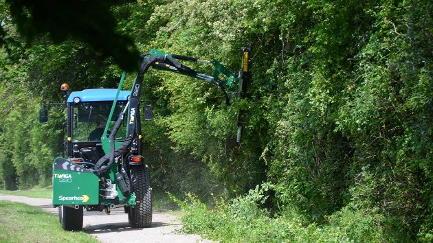 Boom mower for compact tractor reaches in and cuts branches