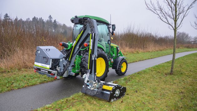 Small tractor with boom mower drives on bike path and mows grass in verges