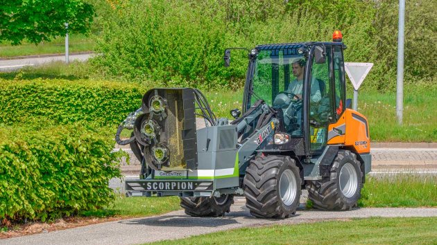 Hedge trimmer attachment tool in transport position on loader