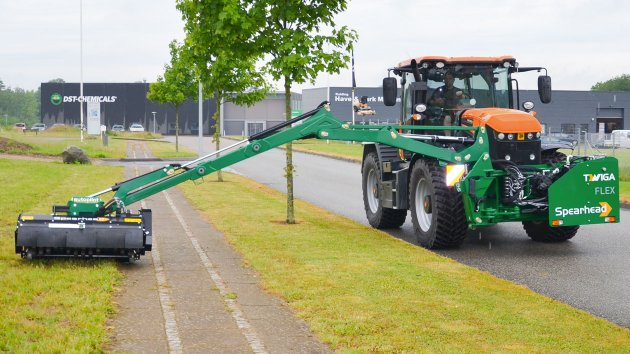 Reach mower for tractor cuts grass on the other side of the sidewalk
