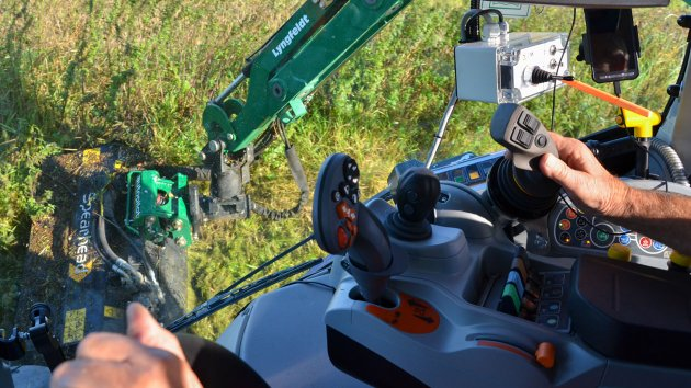The driver controls the boom mower with a joystick