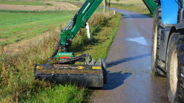 Flail mower head cuts grass in the ditch