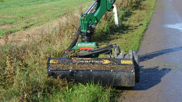 Flail mower attachment cuts grass in the side of the road