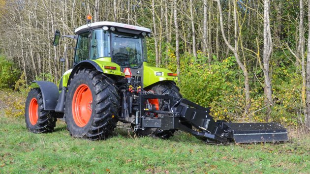 Hydraulic offset flail mower is cutting branches on the ground