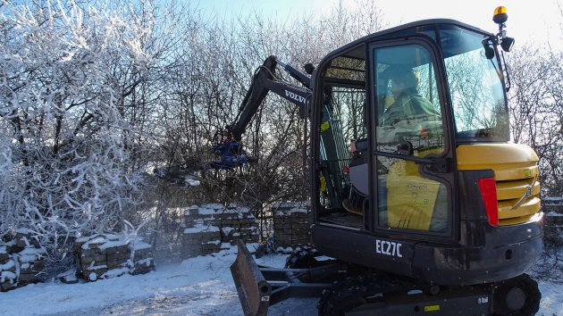 Mini excavator tree saw attachment cuts branches in the snow