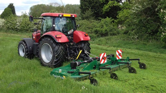 Rotary mower mows a field of grass