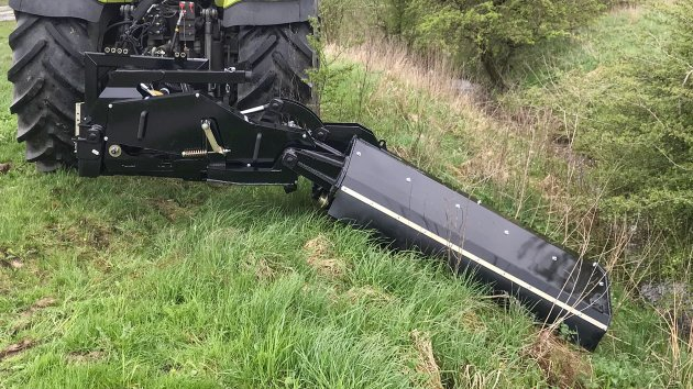 Hydraulic offset flail mower cuts grass in the edge of the road