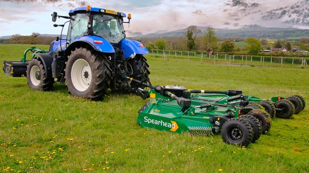 Rotary cutter for tractor mows a field of grass