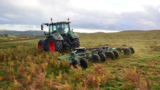 Fallow is being mowed by a rotary cutter mounted on a tractor
