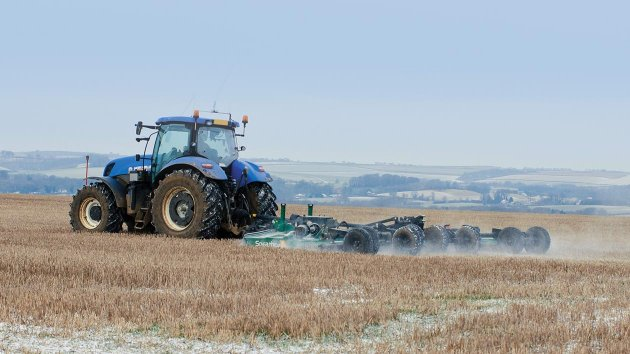 Trailed rotary mower is working a field of fallow