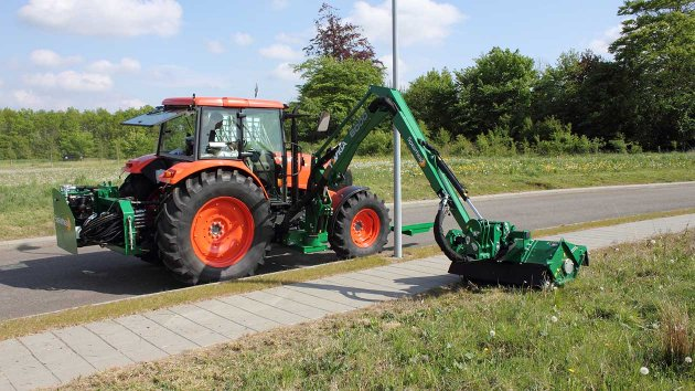 verge mower mounted in the middle of the tractor
