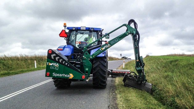 Reach mower mounted on a tractor mows the grass in the verge