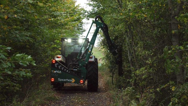 Reach mower with quadsaw cuts branches in forest