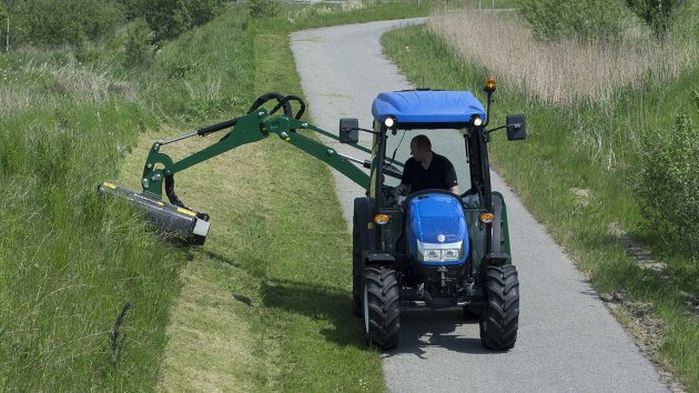 Side arm mower mounted on a compact tractor mows grass uphill