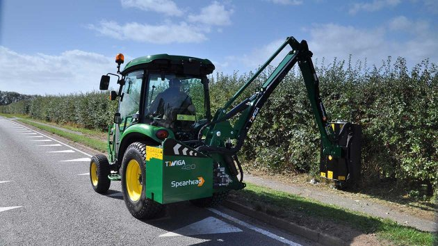 Side arm mower for compact tractor cuts a hedge