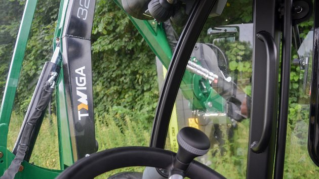 The view from a compact tractor while using a boom mower