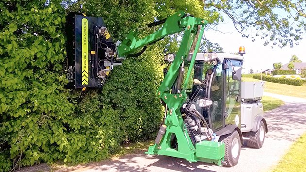 Front mounted arm mower on compact tractor cuts hedge